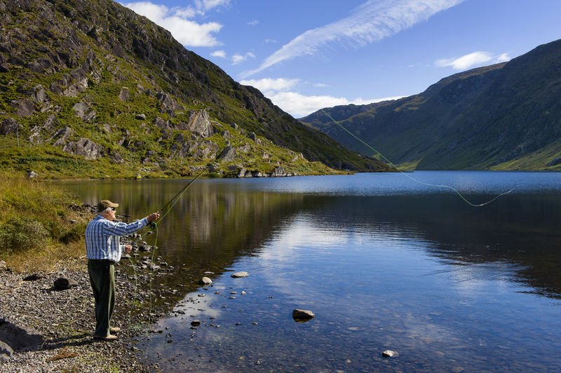 A man fly-fishing on the shore of Glenbeg Lough near Ardgroom