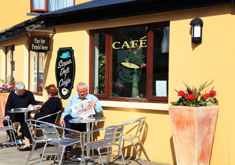 A man reads a newspaper in the sun outside a cafe on the Bear Peninsula